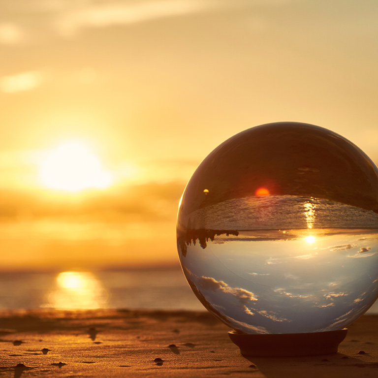 A sphere reflecting the sunset on a beach